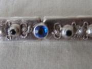 Zilverkleurige broche met blauwe steentjes